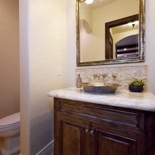 Immagine di un piccolo bagno di servizio classico con ante con bugna sagomata, ante in legno bruno, WC monopezzo, pareti beige, pavimento in travertino, lavabo a bacinella, top in pietra calcarea e pavimento beige