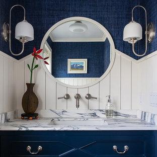 Cette photo montre un WC et toilettes bord de mer avec des portes de placard bleues, un mur bleu, un lavabo encastré et un plan de toilette blanc.