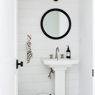 Small country powder room in New York with white walls, white floor, mosaic tile floors and a pedestal sink.
