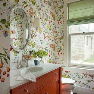 Modelo de aseo tradicional, de tamaño medio, con puertas de armario naranjas, encimera de mármol, paredes multicolor, lavabo bajoencimera, suelo de madera oscura y armarios con rebordes decorativos