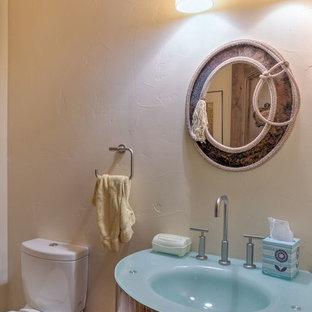 デンバーの中サイズのラスティックスタイルのおしゃれなトイレ・洗面所 (フラットパネル扉のキャビネット、中間色木目調キャビネット、一体型トイレ、ベージュの壁、一体型シンク、ガラスの洗面台) の写真