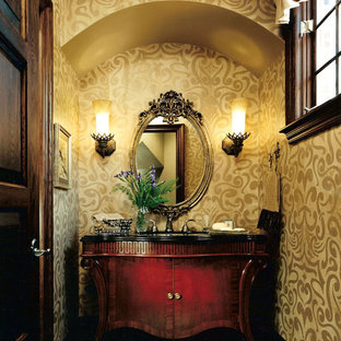 Photo of a mid-sized traditional powder room in Detroit with furniture-like cabinets, brown cabinets, a one-piece toilet, beige walls, ceramic floors, a drop-in sink, marble benchtops, beige floor and grey benchtops.