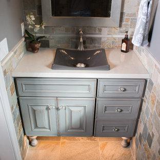 На фото: туалет среднего размера в стиле рустика с фасадами с выступающей филенкой, раздельным унитазом, разноцветной плиткой, серыми стенами, полом из сланца, настольной раковиной, столешницей из гранита, искусственно-состаренными фасадами и каменной плиткой