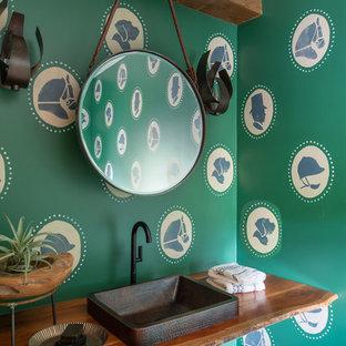 Idée de décoration pour un WC et toilettes champêtre avec un mur vert, un sol en bois foncé, une vasque, un plan de toilette en bois, un sol marron et un plan de toilette marron.