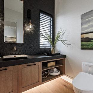 Идея дизайна: туалет в стиле кантри с фасадами в стиле шейкер, светлыми деревянными фасадами, унитазом-моноблоком, черной плиткой, белыми стенами, светлым паркетным полом, настольной раковиной, бежевым полом и черной столешницей