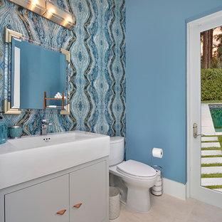 Design ideas for a contemporary cloakroom in Miami with beaded cabinets, grey cabinets, a two-piece toilet, blue walls, a vessel sink and beige floors.