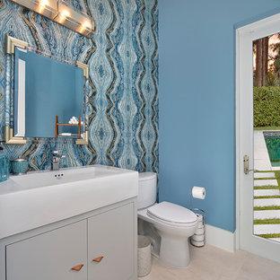 Idee per un bagno di servizio design con ante a filo, ante grigie, WC a due pezzi, pareti blu, lavabo a bacinella e pavimento beige