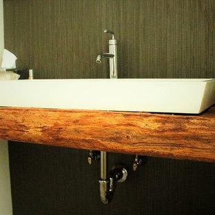 ボストンの中サイズのラスティックスタイルのおしゃれなトイレ・洗面所 (ベージュの壁、ベッセル式洗面器、木製洗面台、黒いタイル、磁器タイル) の写真
