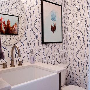 На фото: маленький туалет в стиле кантри с фасадами в стиле шейкер, серыми фасадами, раздельным унитазом, белыми стенами, паркетным полом среднего тона, раковиной с несколькими смесителями, столешницей из искусственного кварца, коричневым полом и белой столешницей с