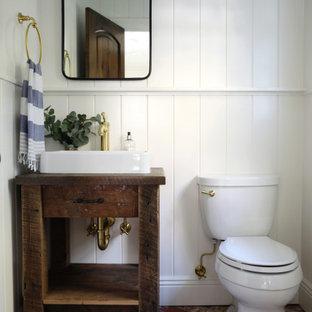 Свежая идея для дизайна: маленький туалет в стиле кантри с коричневыми фасадами, белыми стенами, кирпичным полом, настольной раковиной, столешницей из дерева, красным полом, коричневой столешницей, напольной тумбой и панелями на части стены - отличное фото интерьера