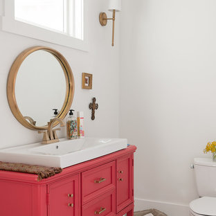 Imagen de aseo clásico renovado, de tamaño medio, con armarios tipo mueble, paredes blancas, suelo de madera pintada, encimera de madera, suelo blanco, baldosas y/o azulejos blancos, sanitario de una pieza, puertas de armario rojas y lavabo sobreencimera
