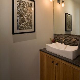 Свежая идея для дизайна: маленький туалет в стиле кантри с настольной раковиной, плоскими фасадами, фасадами цвета дерева среднего тона, серой плиткой, каменной плиткой, белыми стенами и полом из травертина - отличное фото интерьера