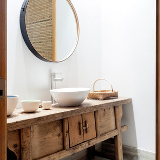 Diseño de aseo asiático con lavabo sobreencimera, armarios tipo mueble, encimera de madera, paredes blancas, puertas de armario de madera clara y encimeras marrones