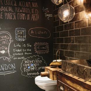 Пример оригинального дизайна: туалет в стиле лофт с фасадами островного типа, искусственно-состаренными фасадами, черной плиткой, черными стенами, бетонным полом, настольной раковиной и серым полом