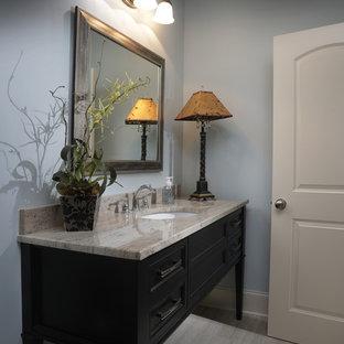 Foto di un bagno di servizio tradizionale di medie dimensioni con consolle stile comò, ante nere, WC a due pezzi, pareti grigie, pavimento in vinile, lavabo sottopiano, top in quarzite e top beige