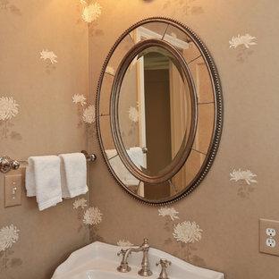 На фото: маленький туалет в классическом стиле с раковиной с пьедесталом, унитазом-моноблоком, темным паркетным полом и бежевыми стенами с