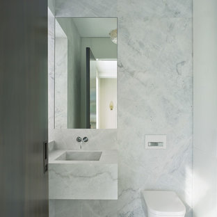 This is an example of a modern cloakroom in New York with glass-front cabinets, white cabinets, a wall mounted toilet, grey tiles, stone slabs, grey walls, marble flooring, a wall-mounted sink, marble worktops and grey floors.
