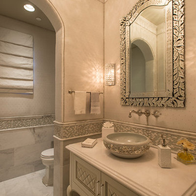 Mid-sized tuscan mosaic tile and gray tile marble floor powder room photo in Phoenix with a vessel sink, furniture-like cabinets, white cabinets, beige walls, a two-piece toilet and solid surface countertops