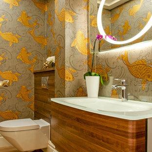 Cette photo montre un WC et toilettes tendance avec un WC suspendu, un placard à porte plane, des portes de placard en bois brun, un mur gris, un sol en bois brun, un plan vasque, un plan de toilette en verre et un sol marron.