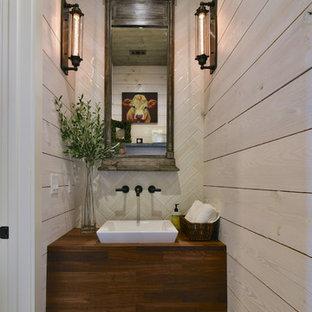 На фото: туалеты в стиле кантри с бежевой плиткой, плиткой из известняка, бежевыми стенами, полом из цементной плитки, настольной раковиной, столешницей из дерева, разноцветным полом и коричневой столешницей