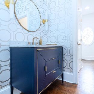 Diseño de aseo papel pintado, tradicional renovado, de tamaño medio, papel pintado, con armarios con paneles con relieve, puertas de armario azules, suelo de madera oscura, lavabo tipo consola, encimera de mármol, suelo marrón, encimeras blancas y papel pintado