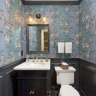 Inspiration for a timeless medium tone wood floor and brown floor powder room remodel in DC Metro with furniture-like cabinets, black cabinets, a two-piece toilet, blue walls, an undermount sink and white countertops