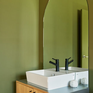 Photo of a contemporary powder room in Melbourne with flat-panel cabinets, light wood cabinets, green walls, a vessel sink and blue benchtops.