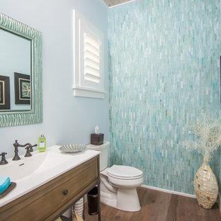 ジャクソンビルの中くらいのビーチスタイルのおしゃれなトイレ・洗面所 (家具調キャビネット、中間色木目調キャビネット、分離型トイレ、青いタイル、緑のタイル、ガラスタイル、青い壁、無垢フローリング、一体型シンク、人工大理石カウンター、茶色い床) の写真