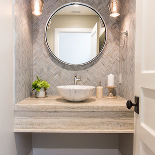 Inspiration for a small coastal beige tile, gray tile and mosaic tile light wood floor and beige floor powder room remodel in Orange County with a vessel sink, travertine countertops and gray walls