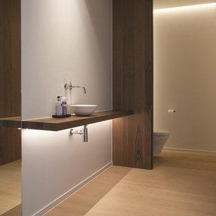 На фото: туалет среднего размера в стиле модернизм с настольной раковиной, столешницей из дерева, инсталляцией, белыми стенами, светлым паркетным полом и коричневой столешницей