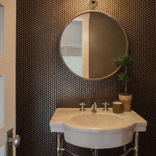 Foto på ett litet vintage toalett, med brun kakel, kakel i metall, bruna väggar, mörkt trägolv, ett piedestal handfat och brunt golv