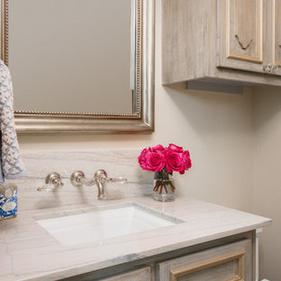 Small traditional cloakroom in Houston with raised-panel cabinets, beige cabinets, a two-piece toilet, beige walls, a submerged sink, quartz worktops, beige worktops, slate flooring and multi-coloured floors.
