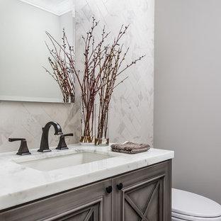 Идея дизайна: туалет в современном стиле с фасадами с утопленной филенкой, искусственно-состаренными фасадами, серой плиткой, каменной плиткой, врезной раковиной, мраморной столешницей, серыми стенами и паркетным полом среднего тона
