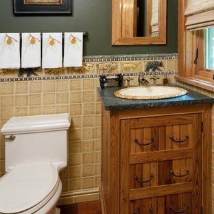 Idées déco pour un petit WC et toilettes classique avec un placard en trompe-l'oeil, des portes de placard en bois brun, un WC à poser, un carrelage jaune, des carreaux de porcelaine, un mur vert, un sol en bois brun, un lavabo posé, un plan de toilette en stéatite et un plan de toilette vert.