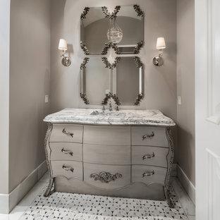 Источник вдохновения для домашнего уюта: огромный туалет в средиземноморском стиле с фасадами островного типа, бежевыми фасадами, унитазом-моноблоком, разноцветной плиткой, мраморной плиткой, бежевыми стенами, полом из мозаичной плитки, монолитной раковиной, мраморной столешницей, разноцветным полом и бежевой столешницей