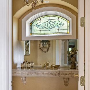 Ispirazione per un ampio bagno di servizio tradizionale con consolle stile comò, piastrelle beige, pareti beige, lavabo sottopiano e top in pietra calcarea