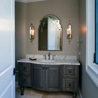 Неиссякаемый источник вдохновения для домашнего уюта: большой туалет в классическом стиле с фасадами с выступающей филенкой, серыми фасадами, бежевой плиткой, мраморной столешницей, серыми стенами, полом из известняка, врезной раковиной и плиткой из листового камня