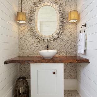 マイアミのビーチスタイルのおしゃれなトイレ・洗面所 (フラットパネル扉のキャビネット、白いキャビネット、ベージュのタイル、石タイル、白い壁、玉石タイル、ベッセル式洗面器、木製洗面台、ベージュの床、ブラウンの洗面カウンター) の写真