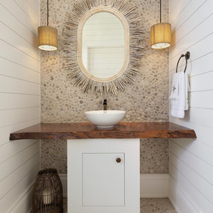 Photo of a nautical cloakroom in Other with flat-panel cabinets, white cabinets, multi-coloured tiles, pebble tiles, white walls, pebble tile flooring, a vessel sink, wooden worktops, multi-coloured floors and brown worktops.