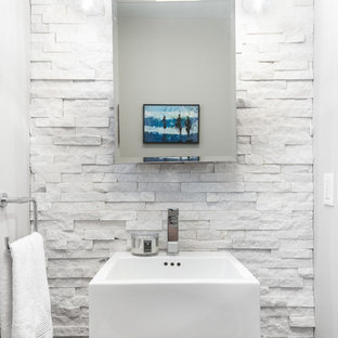 This is an example of a small traditional cloakroom in New York with glass-front cabinets, medium wood cabinets, white tiles, stone tiles, white walls and a vessel sink.