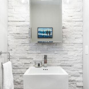 Exemple d'un petit WC et toilettes chic avec un placard à porte vitrée, des portes de placard en bois brun, un carrelage blanc, un carrelage de pierre, un mur blanc et une vasque.