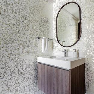 На фото: маленький туалет в современном стиле с плоскими фасадами, фасадами цвета дерева среднего тона, разноцветными стенами, полом из мозаичной плитки, накладной раковиной, столешницей из искусственного камня, белым полом и белой столешницей с