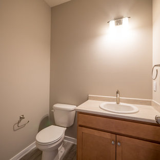Aménagement d'un WC et toilettes craftsman de taille moyenne avec un placard à porte plane, des portes de placard en bois clair, un WC séparé, un carrelage beige, un mur beige, un sol en vinyl, un lavabo posé et un plan de toilette en stratifié.