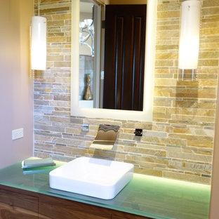 Cette image montre un petit WC et toilettes design avec une vasque, un placard à porte plane, des portes de placard en bois brun et un plan de toilette en verre.