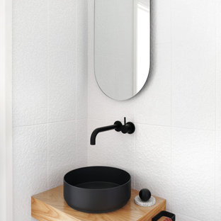 This is an example of a small contemporary powder room in Sydney with white tile, ceramic tile, white walls, a vessel sink and wood benchtops.