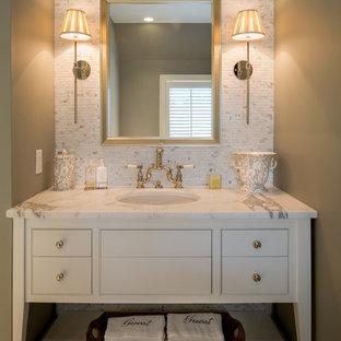 Inredning av ett klassiskt vit vitt toalett, med möbel-liknande, marmorbänkskiva, vit kakel och marmorkakel