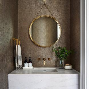 Modelo de aseo clásico renovado, de tamaño medio, con paredes marrones, lavabo bajoencimera, encimera de mármol y encimeras blancas