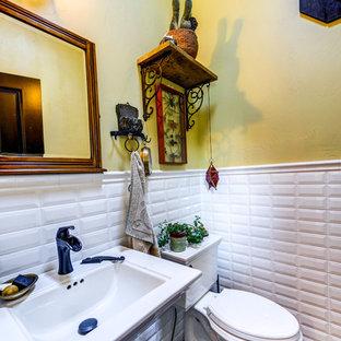 デンバーの小さいラスティックスタイルのおしゃれなトイレ・洗面所 (白いタイル、サブウェイタイル、黄色い壁、スレートの床、ペデスタルシンク、黒い床、白い洗面カウンター) の写真