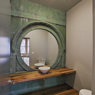 Idée de décoration pour un WC et toilettes urbain de taille moyenne avec une vasque, un plan de toilette en bois, un mur vert, un sol en bois brun, un sol marron et un plan de toilette marron.