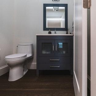 Неиссякаемый источник вдохновения для домашнего уюта: большой туалет в классическом стиле с стеклянными фасадами, серыми фасадами, унитазом-моноблоком, серой плиткой, серыми стенами, паркетным полом среднего тона, врезной раковиной, столешницей из искусственного кварца, коричневым полом и белой столешницей